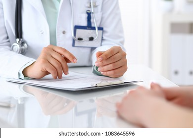 Doctor and patient talking while sitting at the desk in hospital office, closeup of human hands. Medicine and health care concept