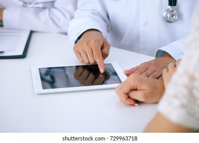 Doctor and  patient talking while sitting at the desk in office. Physician pointing into touch pad computer or tablet. Medicine and health care concept