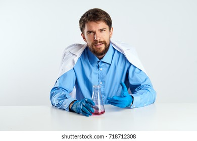 doctor pediatrician in a medical dressing gown sits at a table holding a flask with a pink substance on a light background, medicine, laboratory