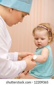 Doctor pediatrician putting a bandage on a little girl's arm