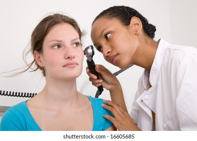 Doctor peering into her patients ear with an instrument