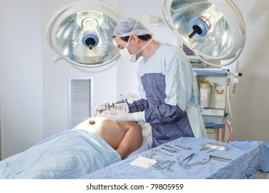 Doctor performing operation on patient in operating room