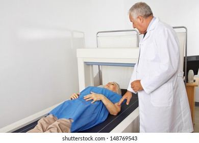 Doctor performing osteodensitometry in radiology to senior patient