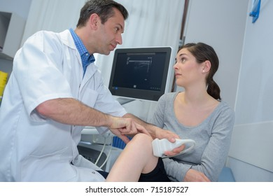 Doctor performing ultrasound on woman's knee