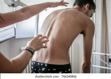 doctor performs a medical examination on a patient diagnosed with scoliosis