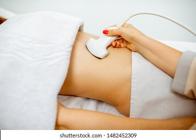 Doctor performs ultrasound examination of a women's pelvic organs or diagnosing early pregnancy at the medical office. Close-up view with no face