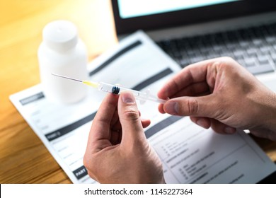 Doctor or physician holding injection needle in dramatic light. Medical research. Health care record document or report paper on table. Vaccine, blood test or flu shot. Malpractice or fake doctor.