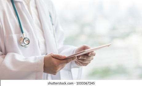 Doctor or physician holding mobile tablet for patient's health record in medical clinic or hospital office for professional online and emergency healthcare assistance service concept
