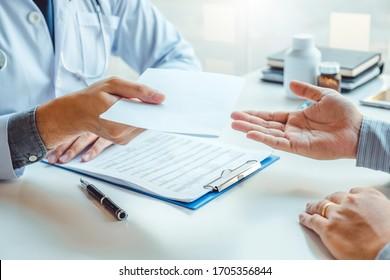 Arzt oder Arzt, der eine Diagnose schreibt und dem männlichen Patienten eine ärztliche Verschreibung gibt