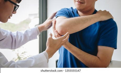 Doctor physiotherapist assisting a male patient while giving exercising treatment massaging the arm of patient in a physio room, rehabilitation physiotherapy concept.