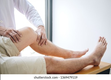 Doctor physiotherapist assisting a male patient while giving exercising treatment massaging the leg of patient in a physio room, rehabilitation physiotherapy concept.