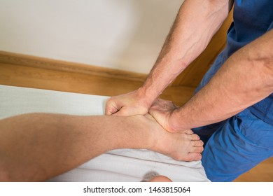Doctor physiotherapist assisting a male patient while giving exercising treatment massaging the astragalus fibula of patient in a physio room, rehabilitation physiotherapy concept.
