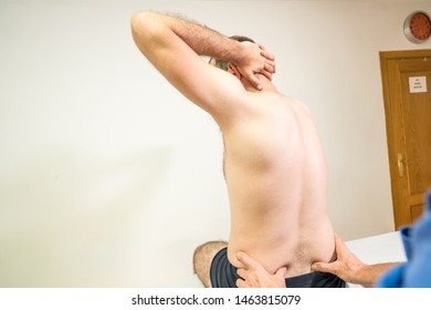 Doctor physiotherapist assisting a male patient while giving exercising vertical sacrum of patient in a physio room, rehabilitation physiotherapy concept.
