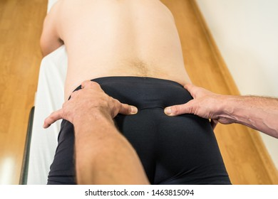Doctor physiotherapist assisting a male patient while giving exercising treatment massaging the sacrum of patient in a physio room, rehabilitation physiotherapy concept.