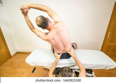Doctor physiotherapist assisting a male patient while giving a sacrum test of patient in a physio room, rehabilitation physiotherapy concept.