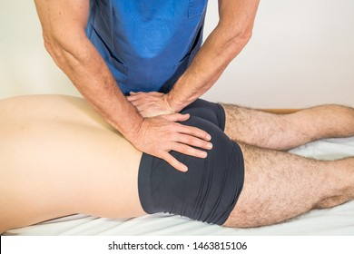 Doctor physiotherapist assisting a male patient while giving exercising treatment rotation sacrum of patient in a physio room, rehabilitation physiotherapy concept.