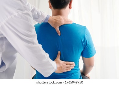 Doctor physiotherapist doing healing treatment on man's back.Back pain patient, treatment, medical doctor, massage therapist.office syndrome
