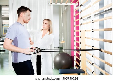 doctor physiotherapist helps a patient to restore movement and function with  gymnastics stretching  and exercises to improve performance