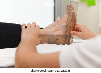 Doctor or physiotherapist measuring active range of motion using manual goniometer