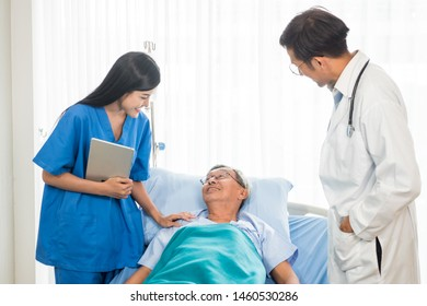 Doctor and physiotherapist talking to elderly patient lying on bed