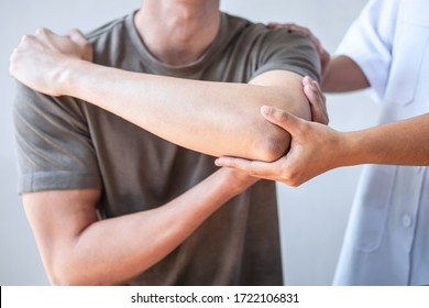Doctor or Physiotherapist working examining treating injured arm of athlete male patient, stretching and exercise, Doing the Rehabilitation therapy pain in clinic. - Shutterstock ID 1722106831