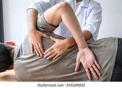 Doctor or Physiotherapist working examining treating injured back of athlete male patient, Doing the Rehabilitation therapy pain in clinic.