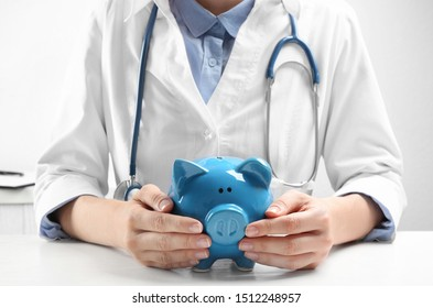 Doctor with piggybank at white table indoors, closeup. Medical insurance concept