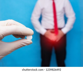 doctor with a pill in his hand from sexually transmitted diseases, in the background a man clings to the lower abdomen he has genital infection and prostate cancer