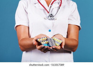 Doctor with pills in hand closeup