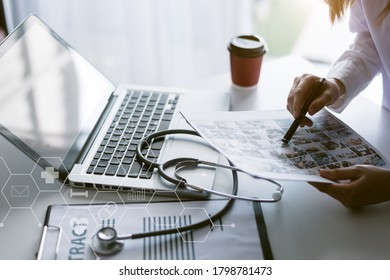 Doctor planning Treatment monograph,with clipboard and Laptop and Stethoscope on white desk ,Interior The hospital blurred background.- Image
