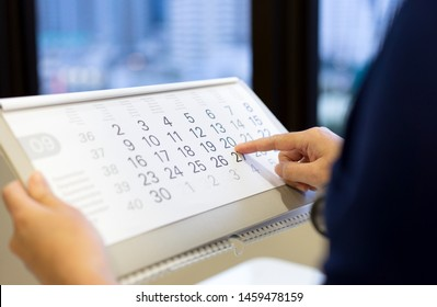 Doctor is pointing the appointment date on the calendar.