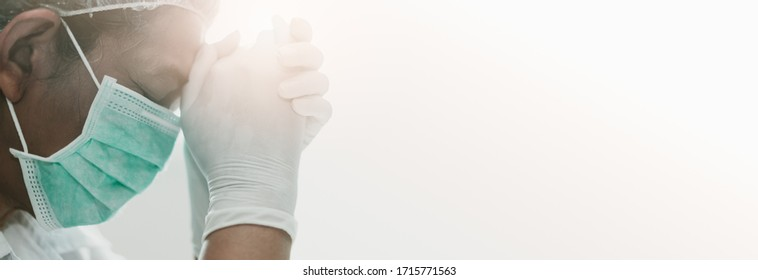 Doctor in PPE suit uniform praying in hospital room with hope.Coronavirus Covid-19.Church online in sunday service. Doctor with faith and praying to GOD.Religion, Medical care during covid-19 crisis. - Shutterstock ID 1715771563