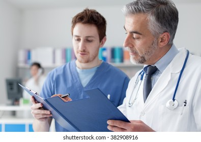 Doctor and practitioner examining patient's medical records on a clipboard