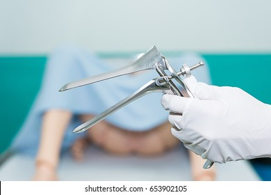 Doctor prepare to diagnosed cervical cancer with speculum on blur background of dummy female patient.