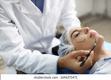 Doctor preparing female patient for cosmetic surgery in clinic