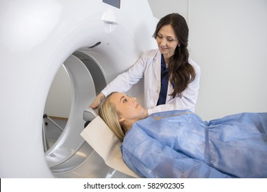 Doctor Preparing Female Patient For MRI Scan In Hospital