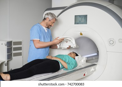 Doctor Preparing Patient For CT Scan