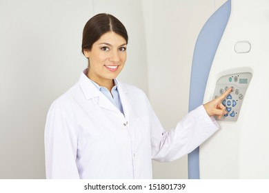 Doctor pressing button with her index finger at MRI machine in radiology