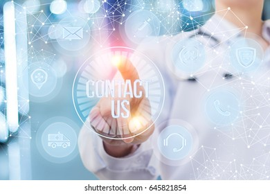 Doctor pressing the contact us button on blurred background.