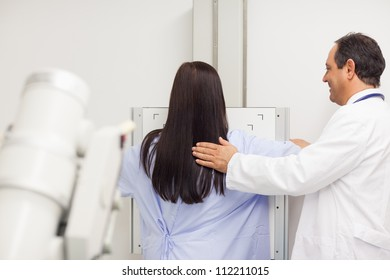 Doctor proceeding a mammography on a patient in an examination room