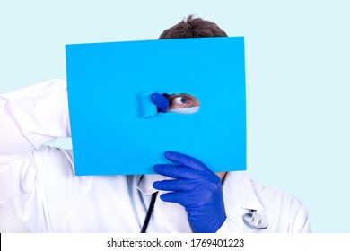 Doctor proctologist looks out from under excerpts of a paper sheet. Medical concept