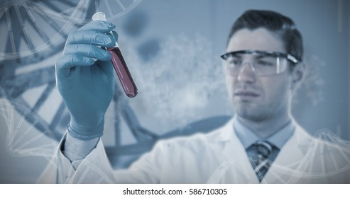 Doctor in protective glasses and surgical mask holding test tube against red dna pattern on screen