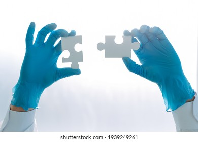 doctor in protective gloves is connecting the pieces of the puzzle.