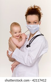 doctor in a protective mask holding a smiling baby on her hands