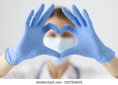 Doctor in protective mask showing heart with his hands closeup. Heart complications after covid19 concept