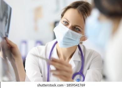 Arzt in medizinischer Schutzmaske, der den Pen in der Klinik auf Röntgenaufnahme zeigt. Pneumonie covid 19 Konzept