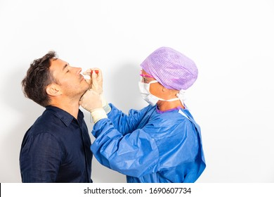 A doctor in a protective suit taking a nasal swab from a person to test for possible coronavirus infection