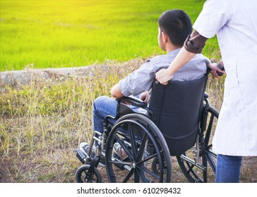 Doctor Pushing Paralyzed man in Wheelchair outdoor in front of  green field background
