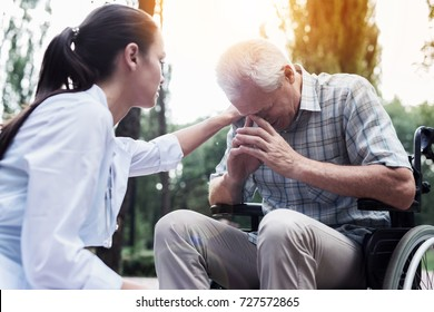The doctor put his hand on the shoulder of the sad old man, who is sitting in a wheelchair in the summer park
