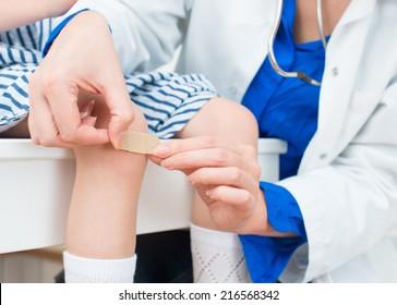 Doctor puts adhesive bandage on child knee.
